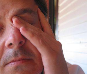 Tired man rubbing his eyes